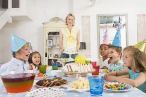 Young children at party sitting at table with mother carrying ca